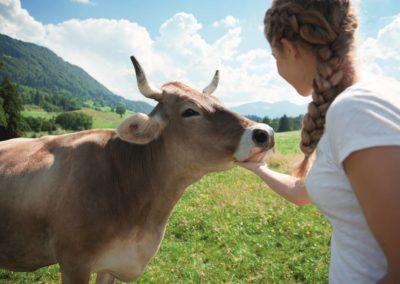 Glückliches Mädchen mit Allgäuer Kuh - Alpenwellness Allgäu © Allgäu GmbH